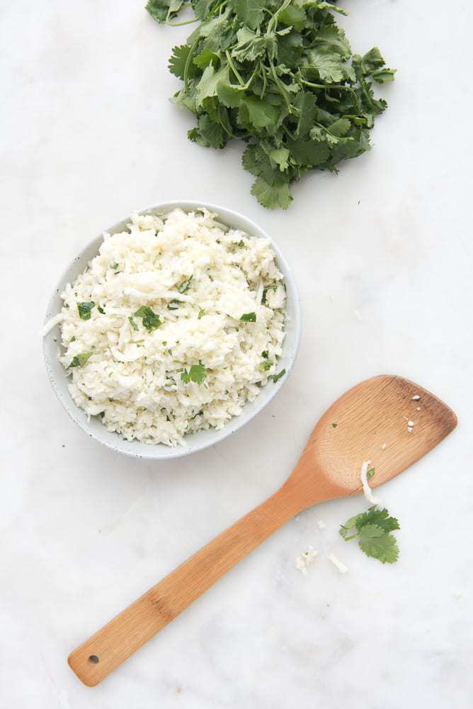 Coconut Cauliflower Rice - a Paleo, gluten-free, Whole30, AIP side dish recipe that takes 10 minutes and is super flavorful. Great with Asian-inspired dishes and for busy nights.