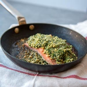 a salmon fillet in a pan with a cashew coating