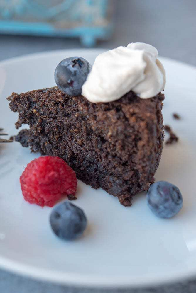 Close up of chocolate cake on a white plate garnished with coconut whipped cream and some fresh blueberries and raspberries