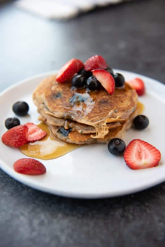AIP Cassava Flour Pancakes on a plate, drizzled with maple syrup and topped with fresh berries