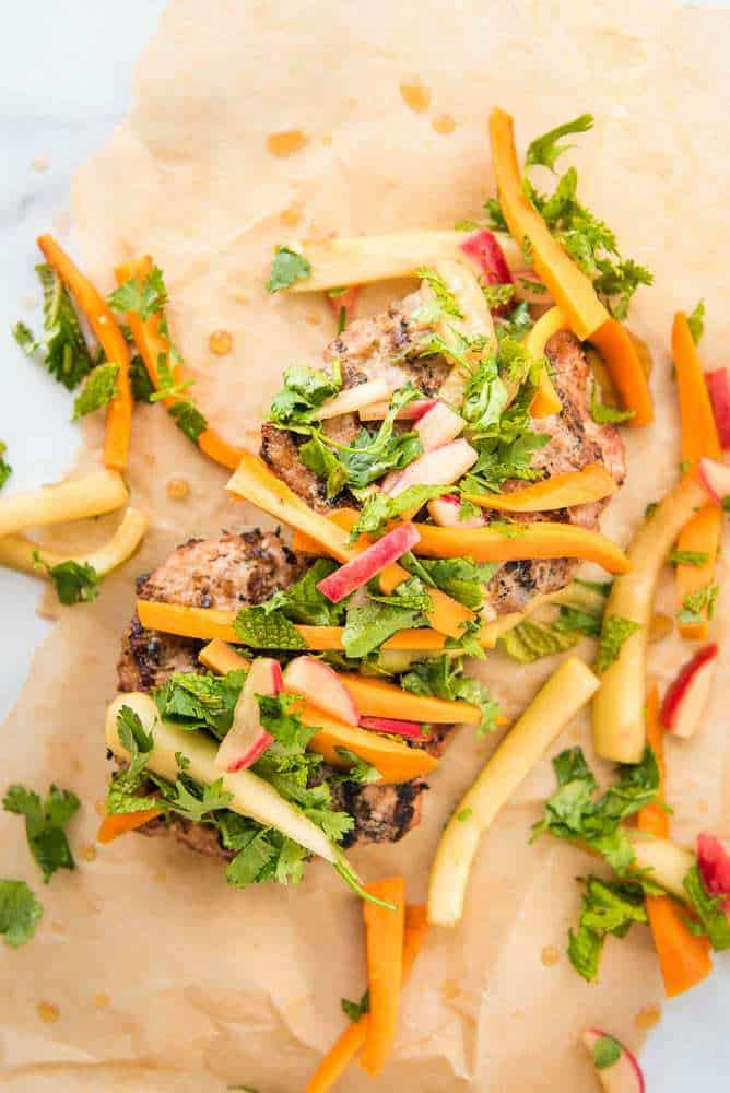 Paleo AIP Banh Mi Burger on parchment paper with the pickled toppings, overhead view
