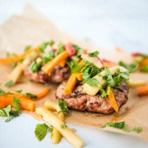 Paleo AIP Banh Mi Burger on parchment paper with the pickled toppings, side view
