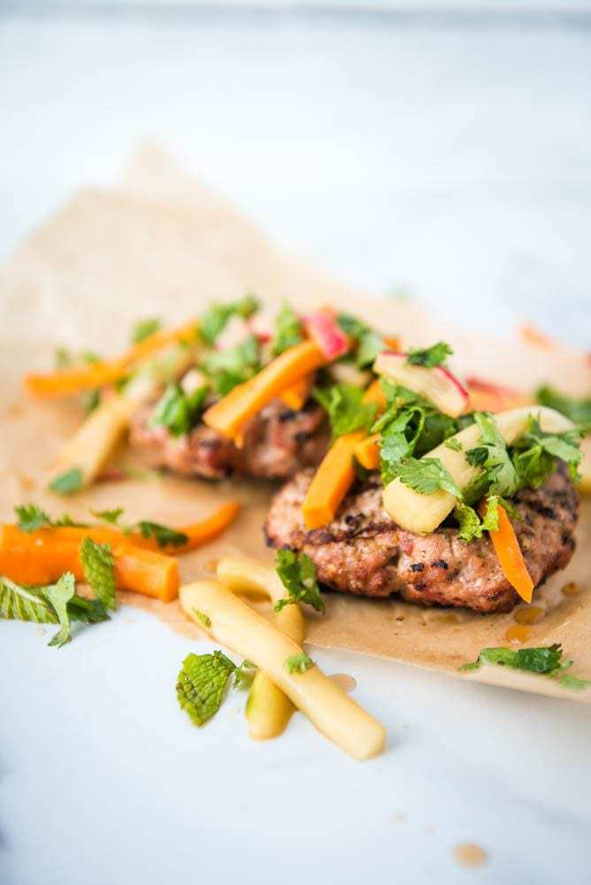 A side view of the Paleo AIP Banh Mi Burger on parchment paper with the pickled toppings