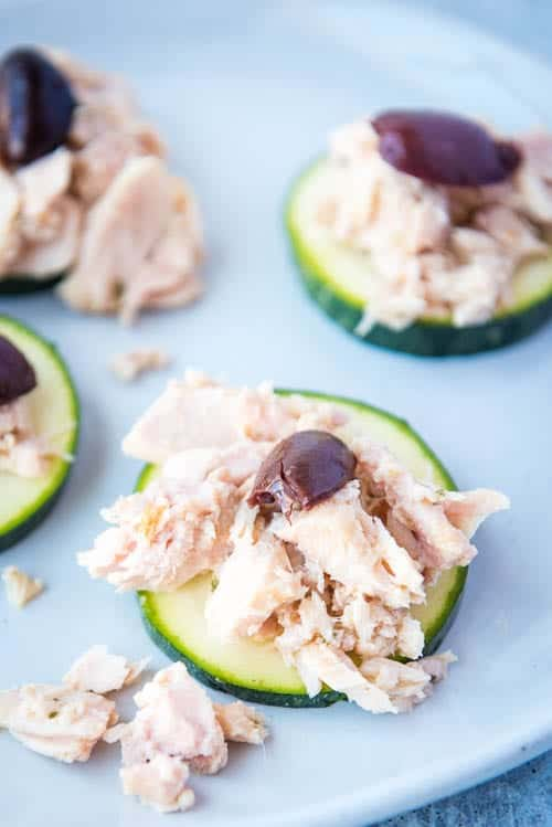 closeup of paleo & aip tuna salad with olives on zucchini rounds as a snack