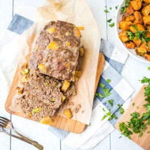 Sweet-and-sour AIP meatloaf sliced and resting on a wooden cutting board - square cropped vertical view from directly above with roasted diced sweet potatoes on the side