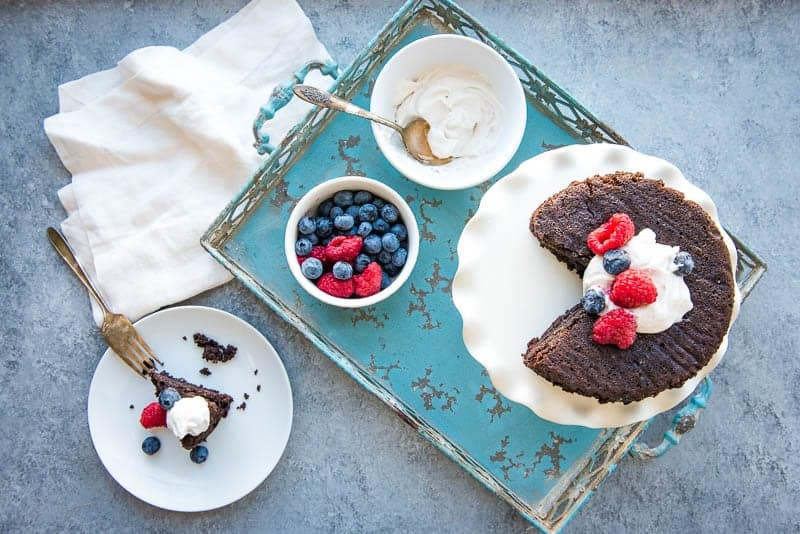 View of Chocolate instant pot cake from above - on an aqua tray with fresh berries  in a small bowl and coconut whipped cream in a separate small bowl