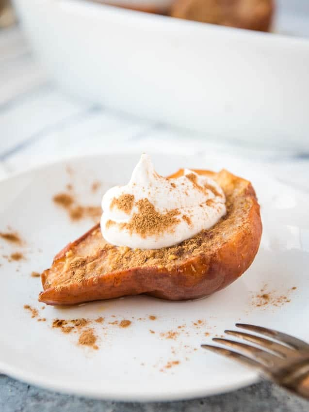 close-up of a baked pear on a plate with a dollop of coconut whipped cream on top