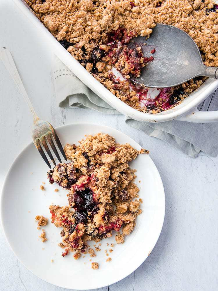 a plate with berry crumble dished out onto it