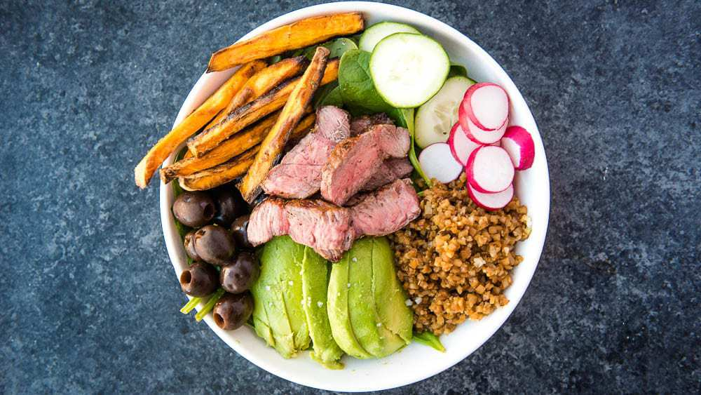 Steak bowl with steak, olives, avocado, cauliflower rice, sweet potato fries, cucumbers, spinach, and radishes on a white plate