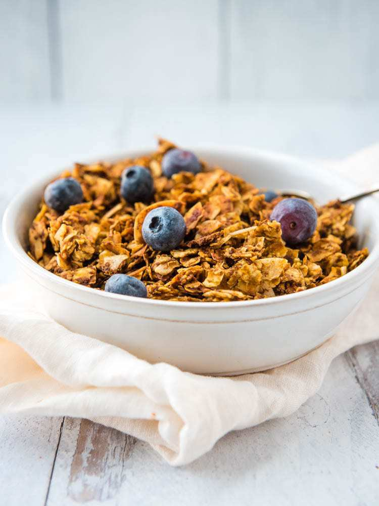 Pumpkin granola from the side in a bowl topped with blueberries