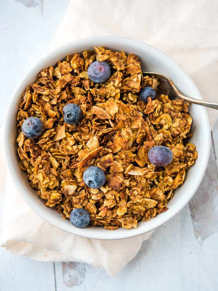 tigernut pumpkin granola from above, in a bowl with blueberries