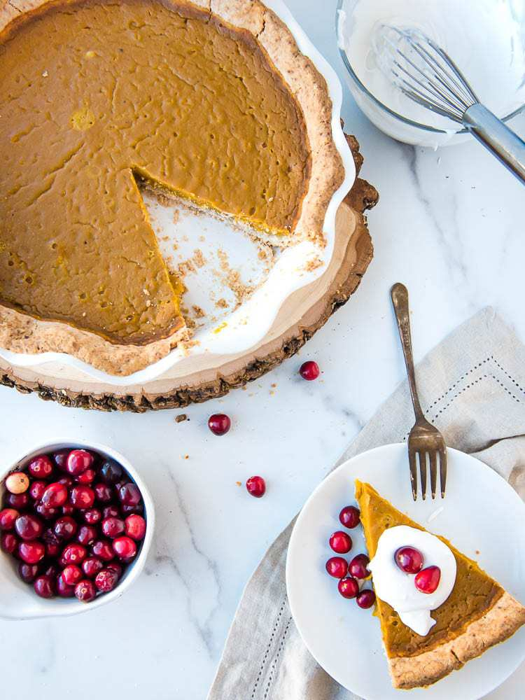 An overhead view of a slice of pumpkin pie with a topping of whipped cream and fresh cranberries and the rest of the pumpkin pie as well