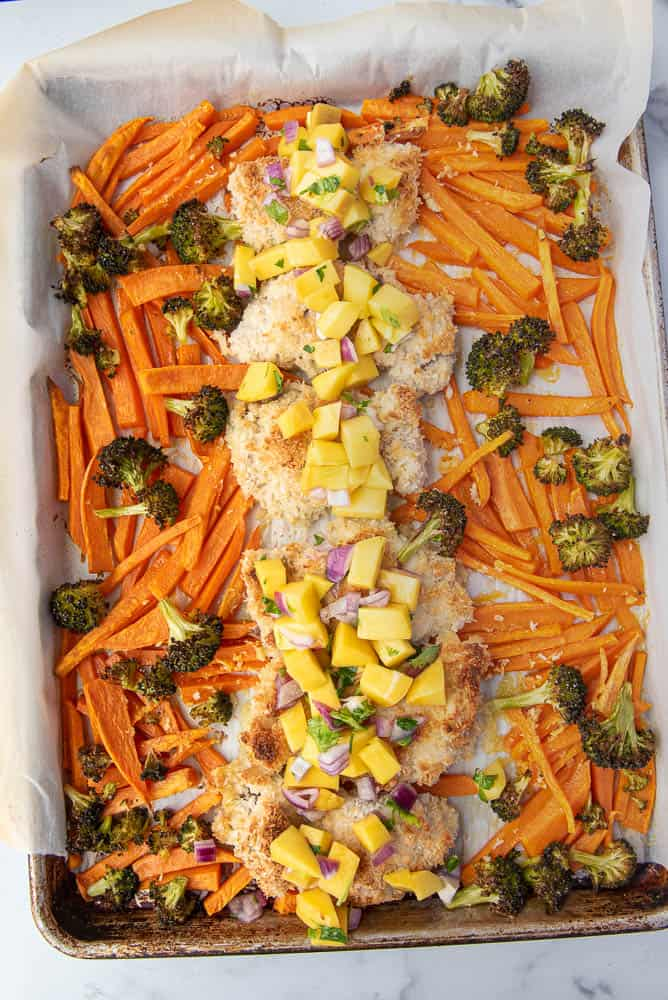 Sheet pan coconut chicken after cooking with mango salsa piled on top