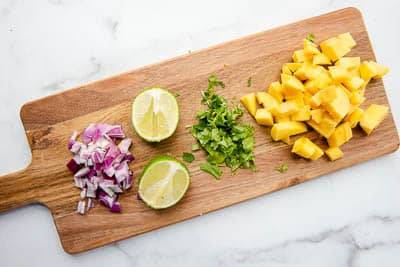 Mango salsa ingredients of red onion, lime, cilantro, and mango