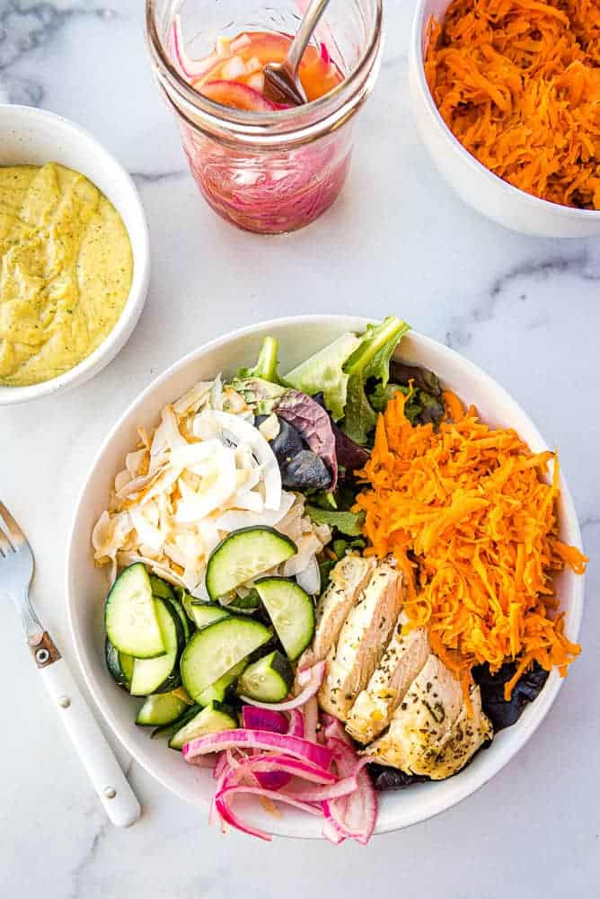 the finished Thai Chicken salad from above with a bowl of mango dressing, the pickled onions, and a bowl of the grated sweet potatoes