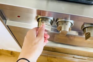 A hand reaching out to turn the dial on the oven to Bake