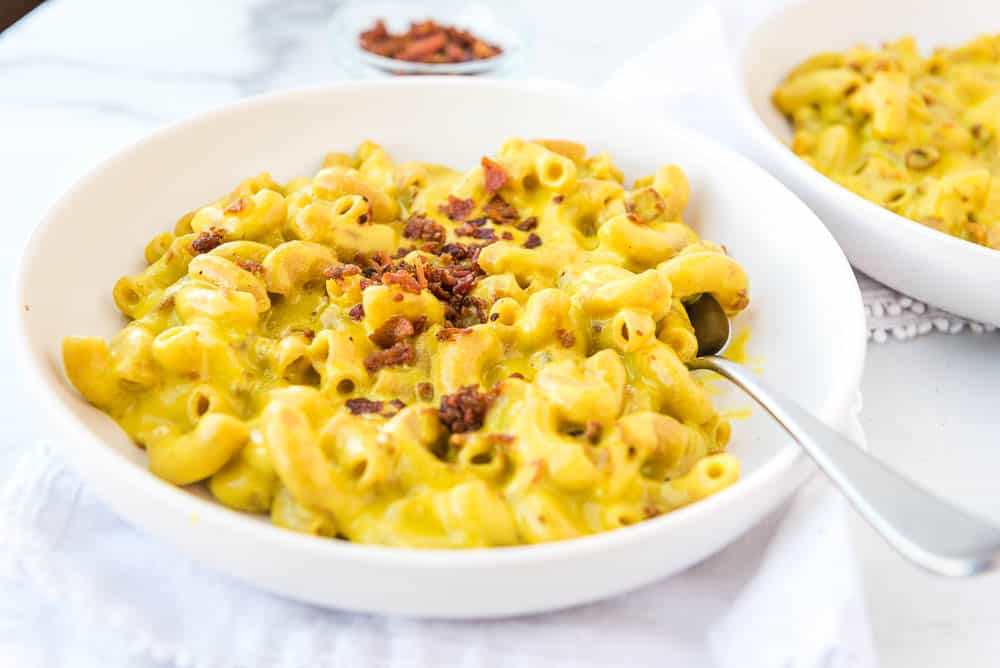 AIP mac and cheese on a plate from the side, sprinkled with bacon bits