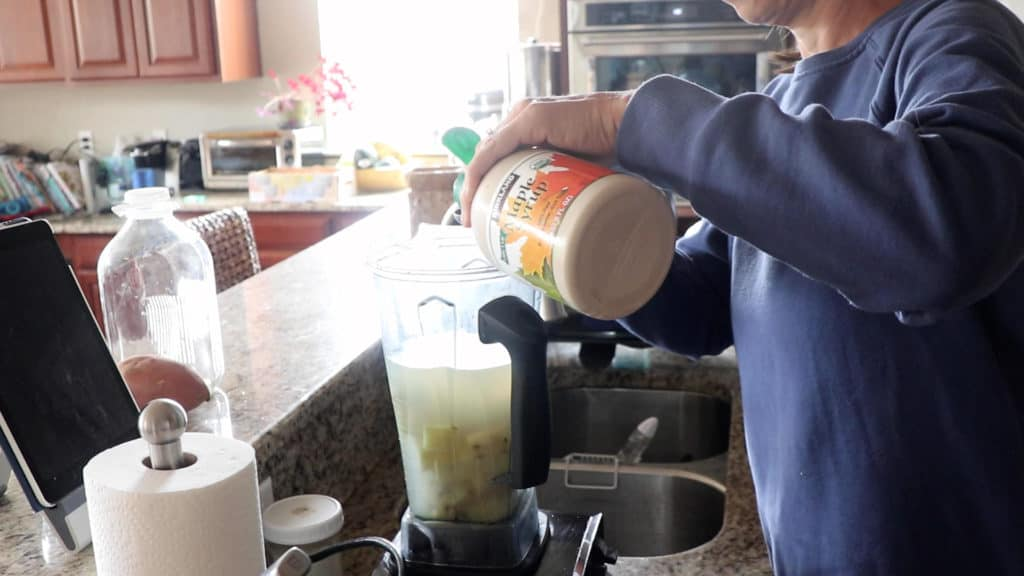 adding maple syrup to the cooked potatoes and water in the blender